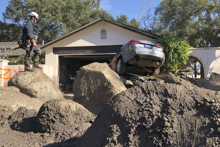 Rescue workers search homes in Montecito, Calif., after mudslides devastated the area on January 13, 2018.