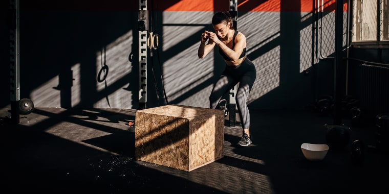 One fit woman box jumping in the gym