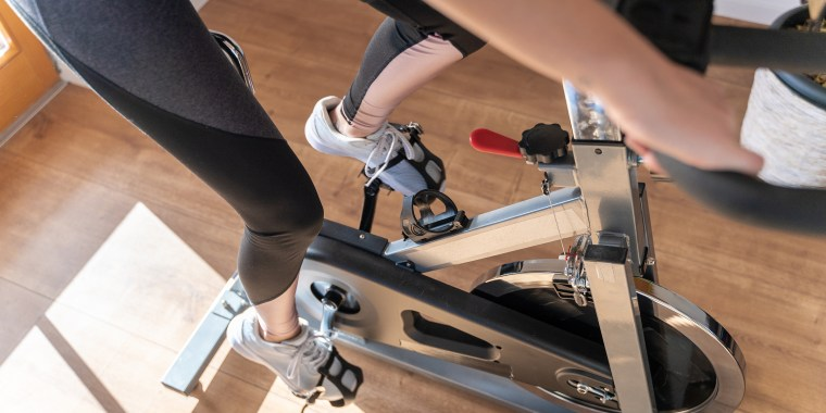 Low section of woman on exercise bike at home