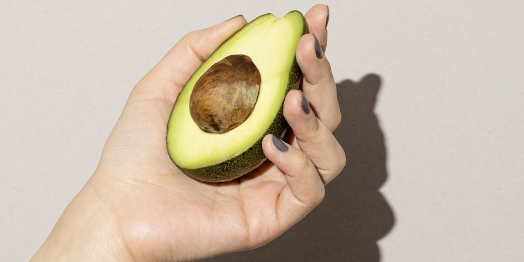 Hand holding half avocado