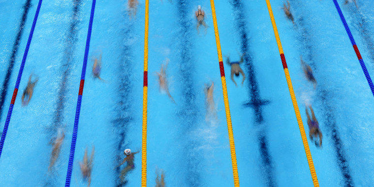 Swimmers warm up before competition at the 2020 Summer Olympics on Sunday, July 25, in Tokyo.
