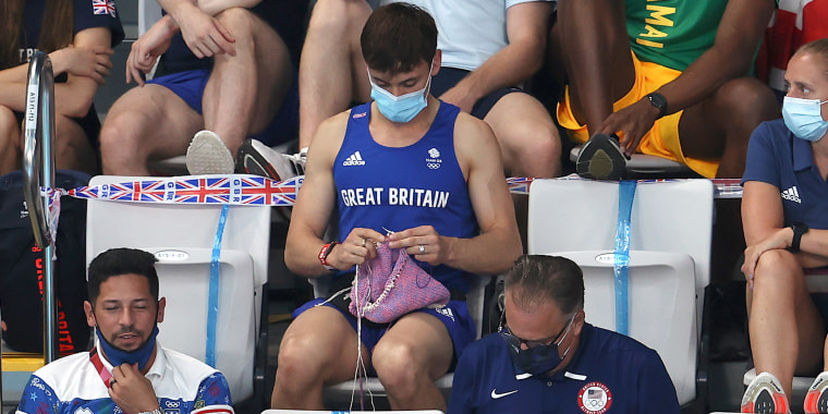 Tom Daley knits in the stands.