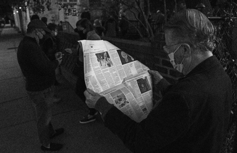 Image: John Winthrop reads a newspaper as he waits to vote in Charleston, S.C., on Nov. 3, 2020.
