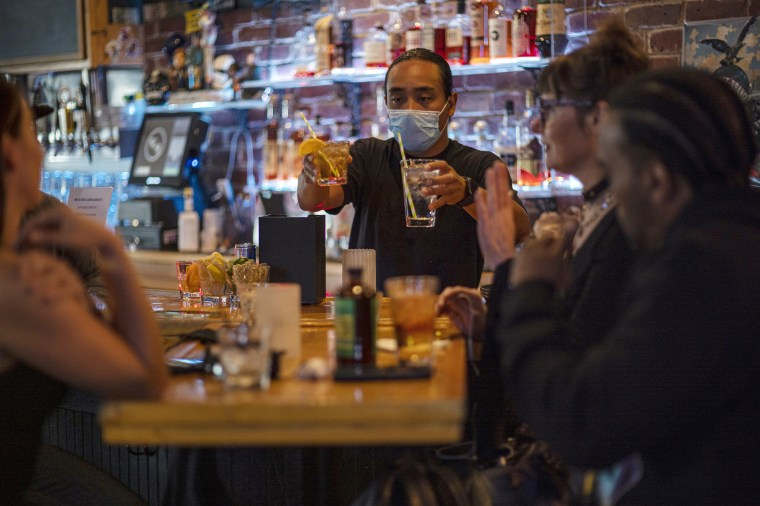 Image: A bartender serves drinks in a bar in San Francisco on May 6, 2021.