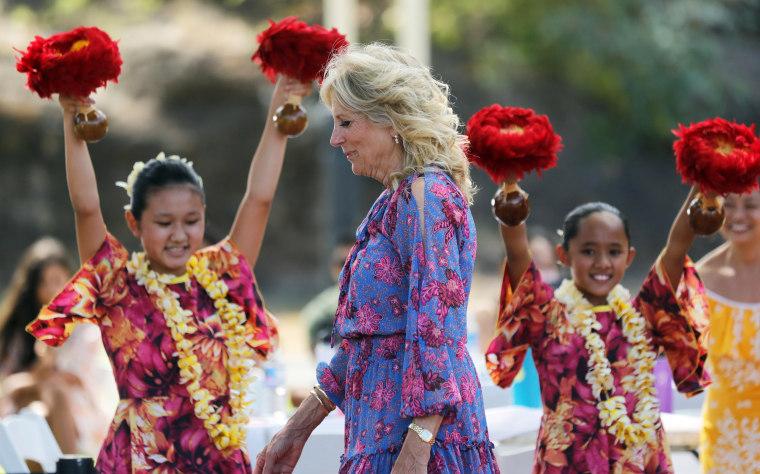 First lady Jill Biden walks past hula dancers with Ka Pa Nani o Lilinoe during a barbecue at Joint Base Pearl Harbor-Hickam, Hawaii, on July 25, 2021.