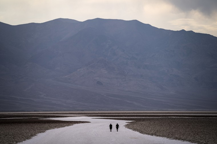 People walk on salt flats in Badwater Basin on July 11, 2021, in Death Valley National Park, Calif.