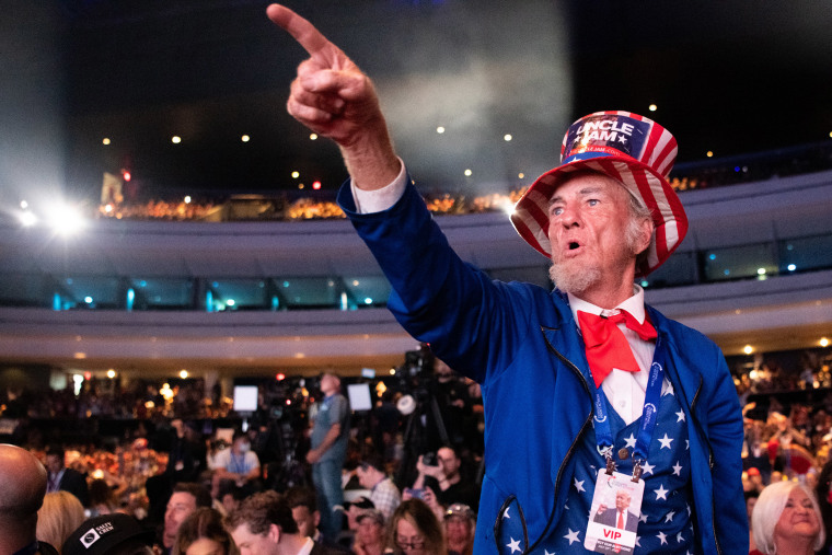 Image: A man points towards the stage ahead of former President Donald Trump's appearance at the Rally To Protect Our Elections conference on July 24, 2021 in Phoenix.