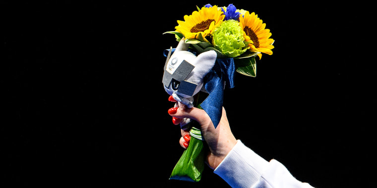 a woman's hand with red fingernails holds a bouquet of flowers against a black background