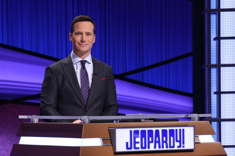 """Mike Richards on the set of """"Jeopardy"""" in blue suit."""