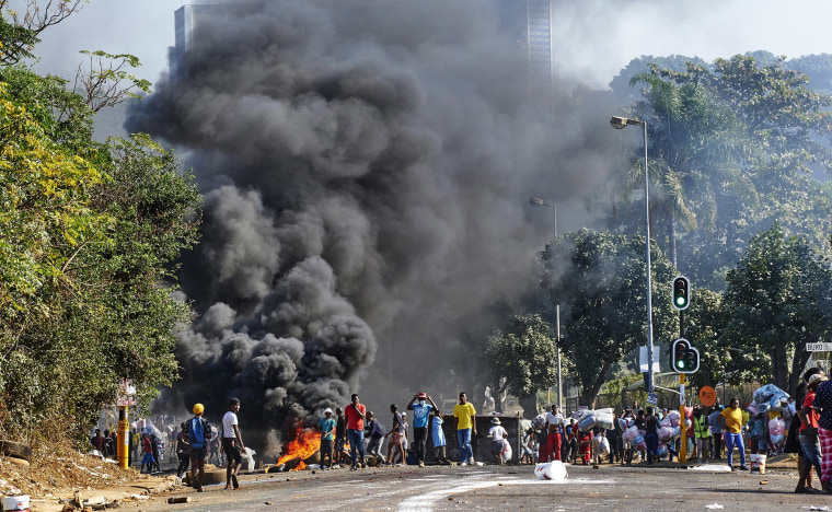 Image: Looters outside a shopping centre alongside a burning barricade in Durban, South Africa