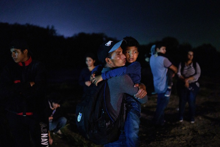 Honduran Eric Villanueva, 31, holds his son Eric, 7, while waiting to be led to a United States Border Patrol processing area after crossing the US-Mexico border on a raft into the United States in Roma, Texas, late on July 9, 2021.