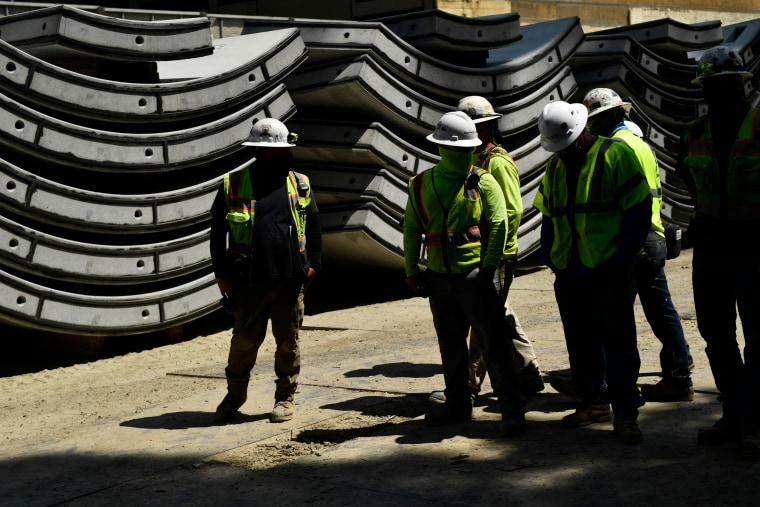 Construction workers stand in front of wall sections for the Metro Purple Line subway extension tunnel project on June 3, 2021, in Los Angeles.