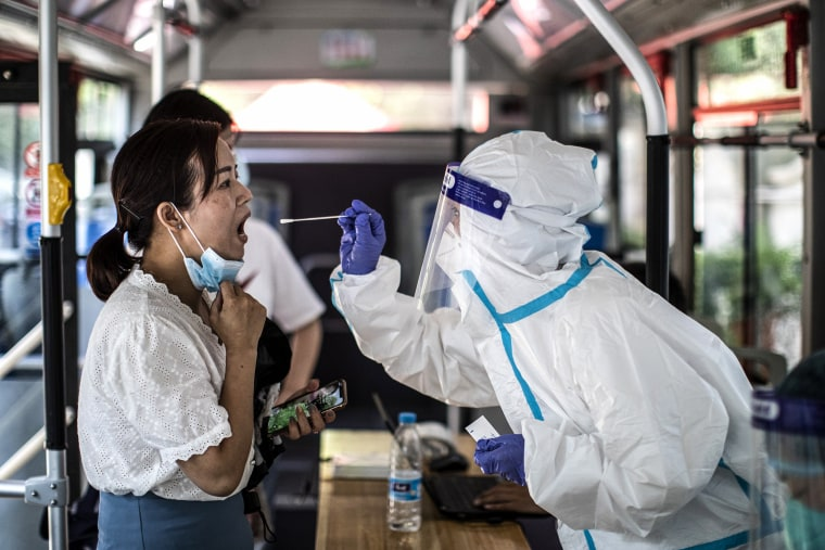 Image: A medical worker takes samples during a mass Covid-19 test in a residential block on Aug. 3, 2021 in Wuhan, Hubei Province, China.
