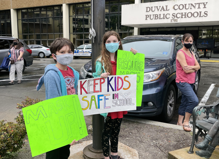 Will and Lila Hartley demonstrate for masks outside a school board meeting.