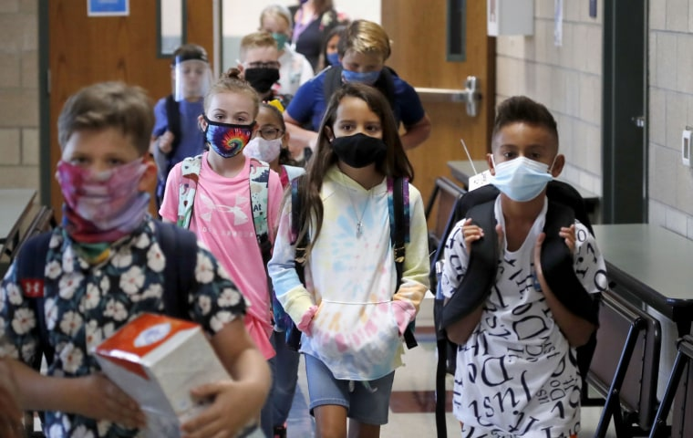 Wearing masks to prevent the spread of Covid, elementary school students walk to classes to begin their school day in Godley, Texas, on Aug. 5, 2020.