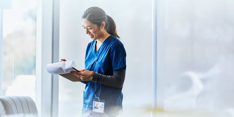 Smiling female nurse examining document in hospital lobby