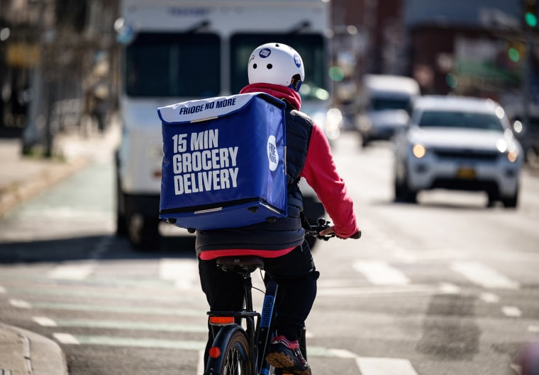 An employee rides a bike to deliver groceries from 'Fridge No More' on March 31, 2021 in Brooklyn, N.Y.