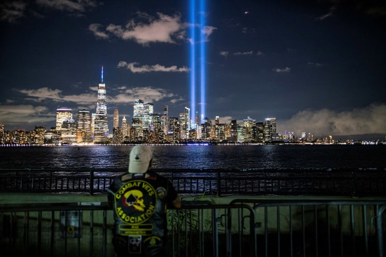 Image: A man looks at The Tribute in Light installation from Liberty State Park, marking the 19th anniversary of the 9/11 attacks in New York City, as seen from Jersey City