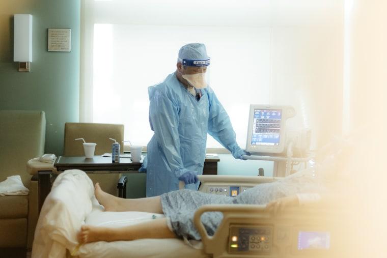 A nurse checks on a patient in the ICU Covid-19 ward at NEA Baptist Memorial Hospital in Jonesboro, Ark., on Aug. 4, 2021.