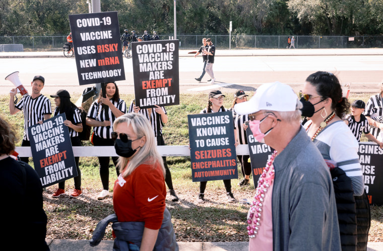 Image: Anti-vaccine protesters shout and wave signs as health care workers wait to enter the Raymond James Stadium before the Super Bowl in Tampa, Fla., on Feb. 7, 2021.