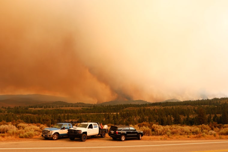 People watch as the Tamarack fire burns unchecked due to drought conditions and gusty winds on Markleeville, Calif., on July 17, 2021.