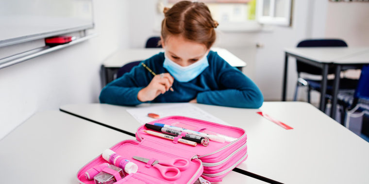 Eight-year-old Anna sits at a table in front of an exercise sheet during a German lesson, with a pink pencil case in front of her