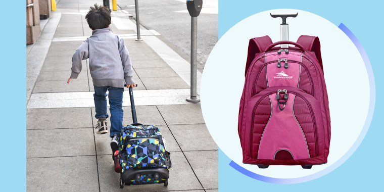 A Chinese boy runs up a sidewalk pulling a kid's rolling backpack in Chinatown in San Francisco, California and a pink High Sierra rolling backpack