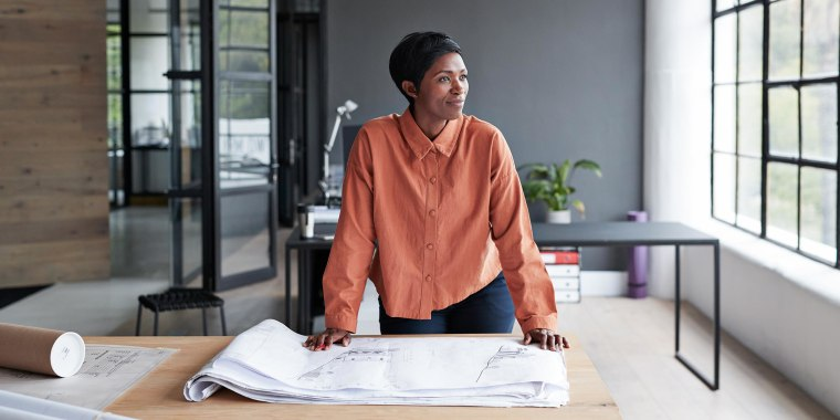 Female entrepreneur looking away while standing by table at workplace