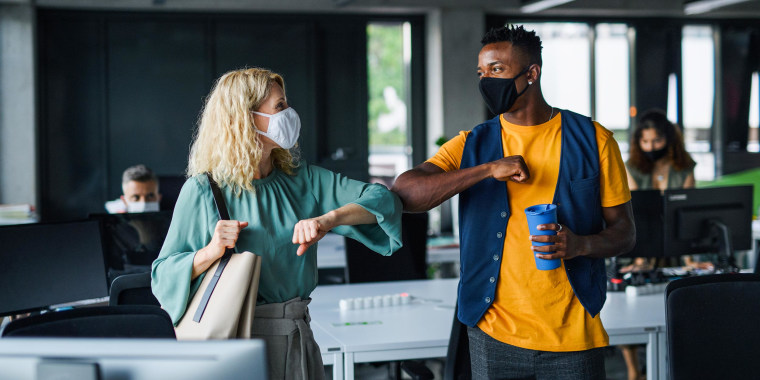 Two coworkers inside an office wearing face masks, bumping elbows
