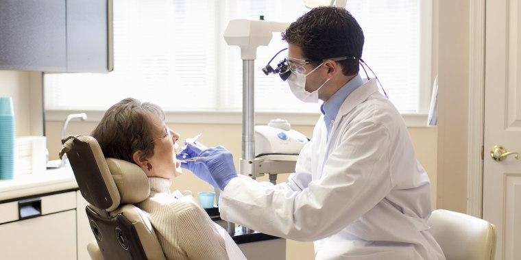 Dentist examines teeth of female patient.