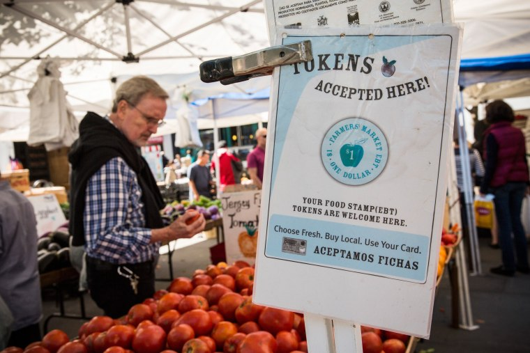 Image: A sign displays that a shop accepts Electronic Benefits Transfer, more commonly known as Food Stamps, in the GrowNYC Greenmarket in Union Square
