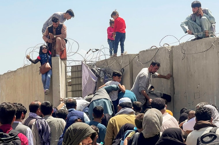 A man pulls a girl to get inside Hamid Karzai International Airport in Kabul, Afghanistan, on Aug. 16, 2021.