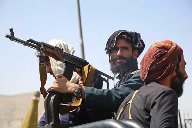Taliban fighters stand guard in a vehicle along the roadside in Kabul on Aug. 16, 2021.
