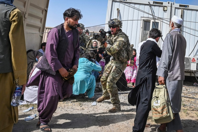 A U.S. soldier points his gun towards an Afghan passenger at Hamid Karzai International Airport in Kabul on Aug. 16, 2021.