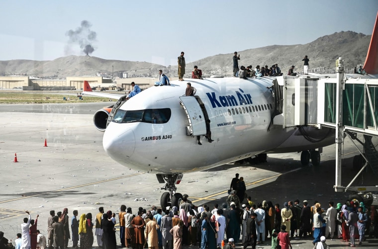 Afghan people climb atop a plane as they wait at Hamid Karzai International Airport in Kabul on Aug. 16, 2021.
