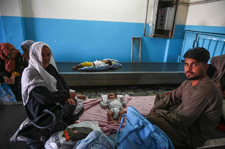 Afghan families wait by the luggage conveyor belt inside Hamid Karzai International Airport in Kabul on Aug. 16, 2021.