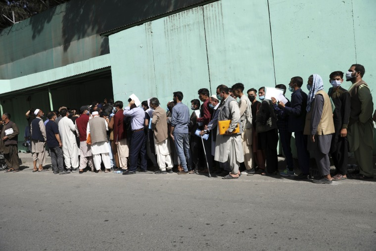 Afghans wait in long lines for hours to get visas in front of the Iranian embassy in Kabul on Aug. 15, 2021.