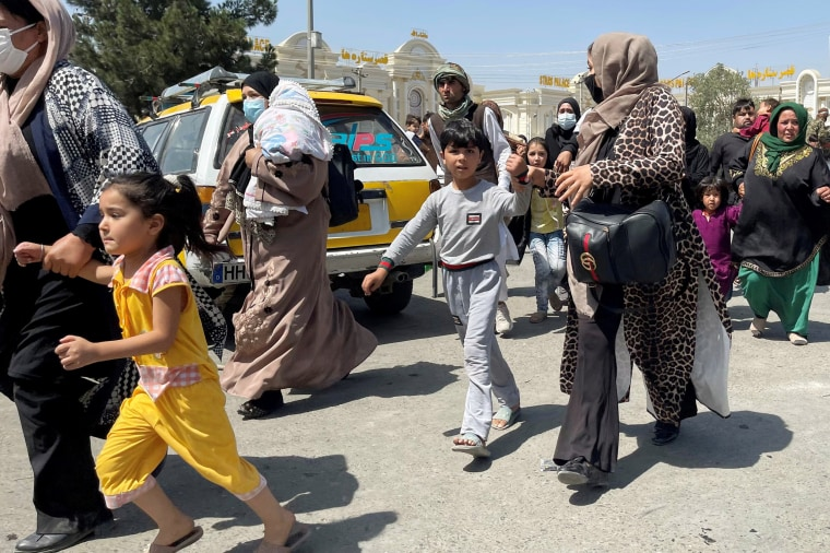 Women with their children try to get inside Hamid Karzai International Airport in Kabul on Aug. 16, 2021.