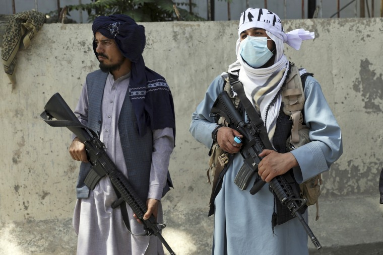Taliban fighters stand guard in the main gate leading to Afghan presidential palace in Kabul on Aug. 16, 2021.