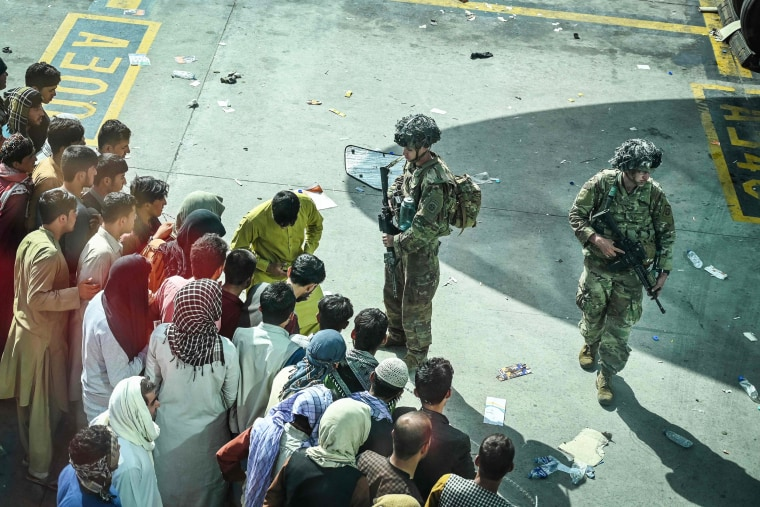 U.S. soldiers stand guard as Afghan people wait at Hamid Karzai International Airport in Kabul on Aug. 16, 2021.