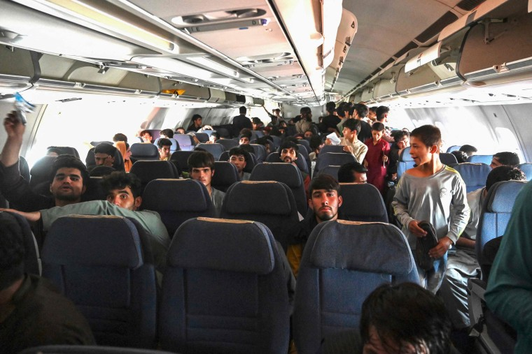 Afghan passengers sit inside a plane as they wait to leave Hamid Karzai International Airport in Kabul on Aug. 16, 2021.