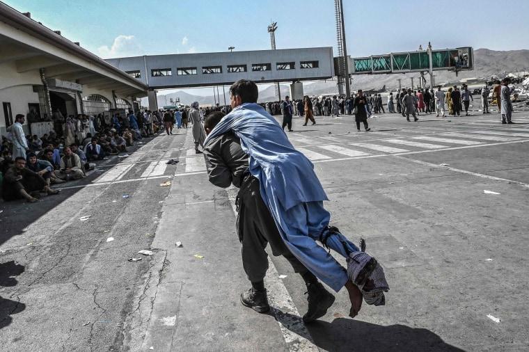 A volunteer carries an injured man at Hamid Karzai International Airport in Kabul on Aug. 16, 2021.