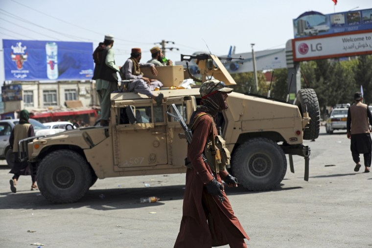 Taliban fighters stand guard in front of the Hamid Karzai International Airport in Kabul on Aug. 16, 2021.