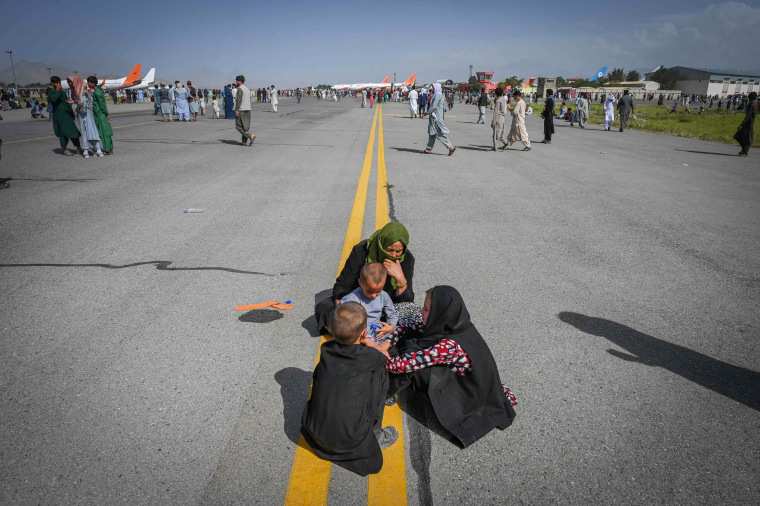Afghan people sit along the tarmac as they wait to leave Hamid Karzai International Airport in Kabul on Aug. 16, 2021.