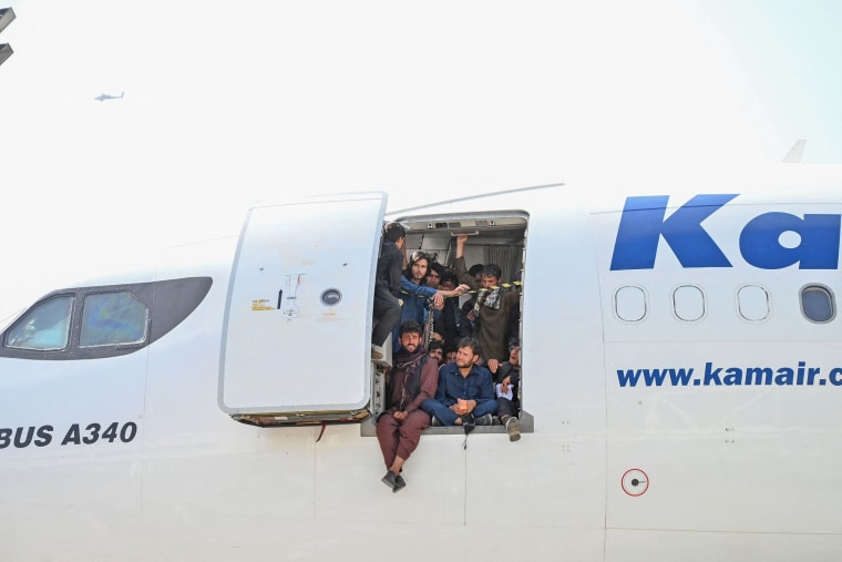 Afghan people climb up on a plane and sit by the door as they wait at Hamid Karzai International Airport in Kabul on Aug. 16, 2021.
