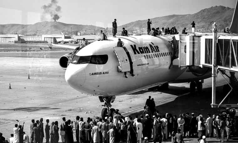 Image: Afghan people climb atop a plane as they wait at the Kabul airport.