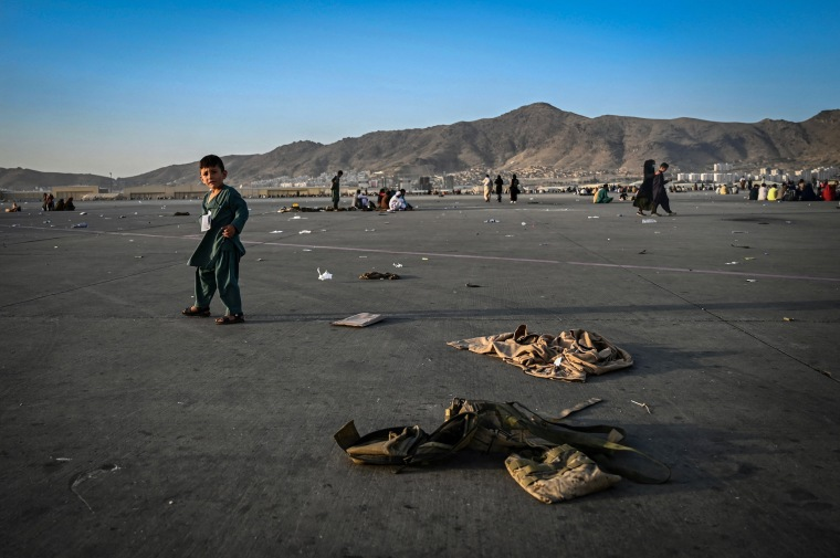 An Afghan child walks near military uniforms as he waits to leave the Kabul airport on Aug. 16, 2021.
