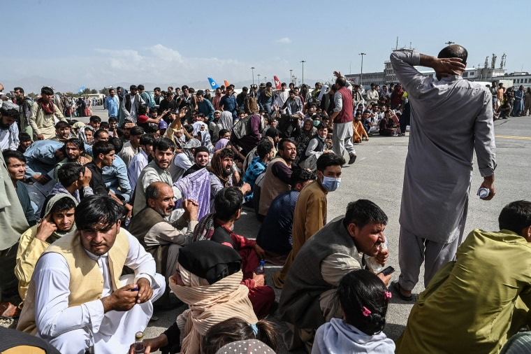 Image: Afghan passengers sit as they wait to leave the Kabul airport in Kabul on Aug. 16, 2021, as thousands of people mobbed the city's airport trying to flee the group's feared hardline brand of Islamist rule.