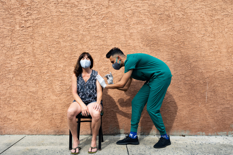 A woman receives a Pfizer Covid-19 vaccination as a booster dose at Skippack Pharmacy in Schwenksville, Pa., on Aug. 14, 2021.