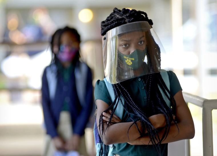 Victoria Dickens wears a mask and face shield as she waits for her class assignment at Summit Elementary School in Summit, Miss., on Aug. 5, 2021
